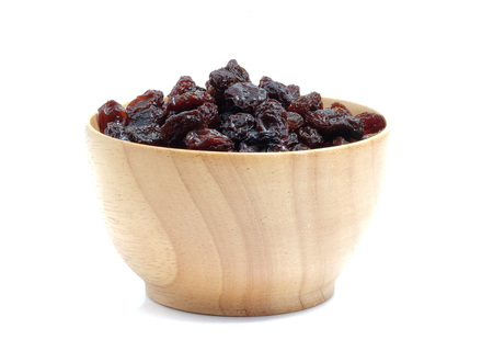 Dried grapes in wood bowl on white background. Stock Photo