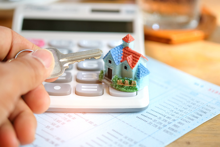 Concept,Key in hand with house model and  calculator on book bank. Stock Photo