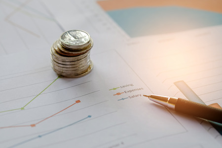 Concept businness,Coins and pen placed on the graph. Stock Photo
