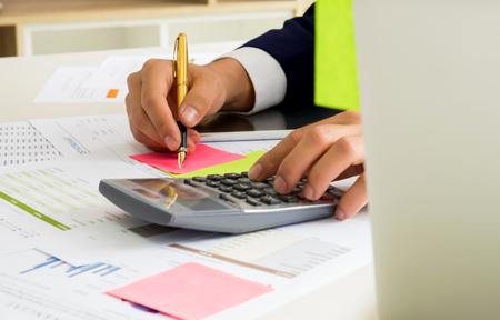 Gli uomini d'affari usano una calcolatrice e scrivono le note su una carta a fogli mobili, la parte anteriore ha un labtop e un grafico sulla scrivania. Archivio Fotografico - 83342205