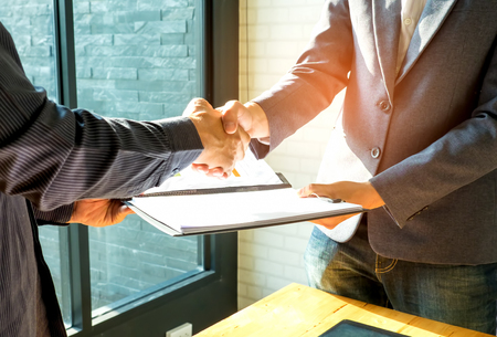 when: Businessmen are shaking hands and exchanging business documents.People shake hands when reaching agreement. Stock Photo