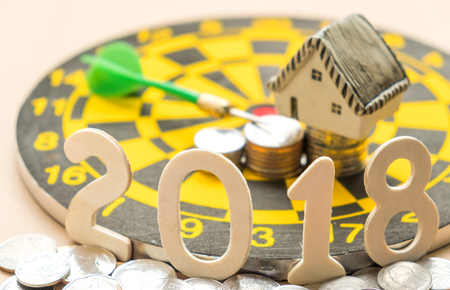 New year concepts,2018 Number on coins with house model and coins place on darth. Stock Photo