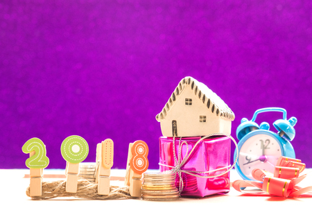 New year concepts,2018 Number with coins and house model on gift,Ribbon and watch placed on the side,violet background.