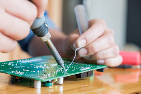 Technician repair circuit board,Use soldering equipment on circuit boards,Repair damaged boards for reuse. Stock Photo