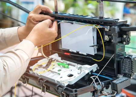 Technicians are installing fiber optic cabinets for high speed internet. Banco de Imagens