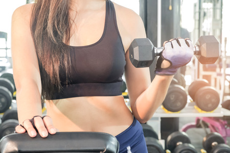 Fitness woman lifting dumbbell in hand.Focus on belly and dumbbell,blurred gym background.