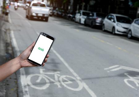 Chiangmai, Thailandia - 26 agosto 2018. Afferrare l'applicazione sul display del telefono intelligente in mano con sfondo sfocato stradale.