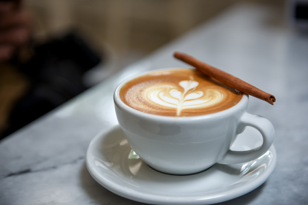Coffee heart late with cinnamon in white cup.Blurred background
