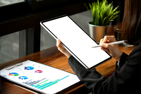 Businesswoman working on blank screen modern tablet  with graphs in office. Stock fotó