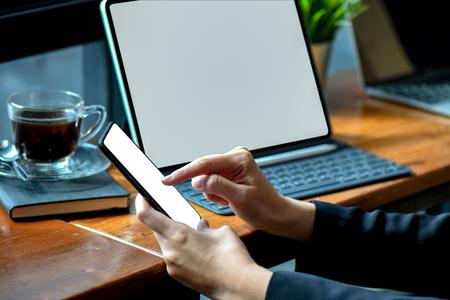 businesswoman working on blank screen smartphone witn modern tablet in office.
