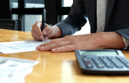 Businessmen are signing the contract documents in the office.