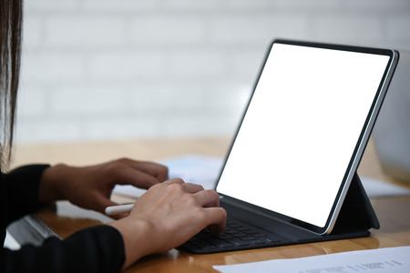 Businesswoman working on white screen tablet computer with graphs on wood table.