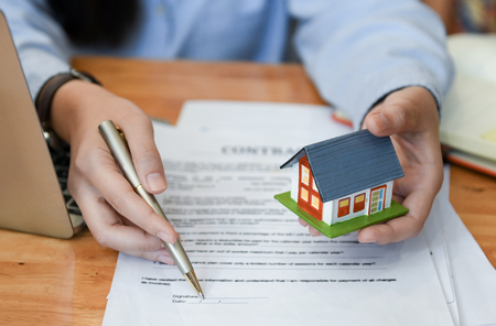 Home salesman holding a pen and model house in hand.Pointing pen at document signing. Stock fotó