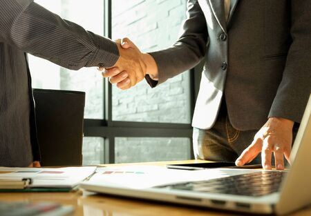 Two businessmen join hands after reaching a business agreement in office. Stock fotó