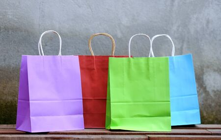 Multi-colored shopping bags placed on a wooden table, for advertising.