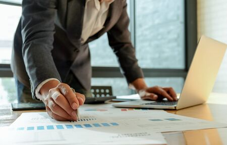 Businessman hand works on a laptop computer and uses a pen pointing at the graph on the desk in office.