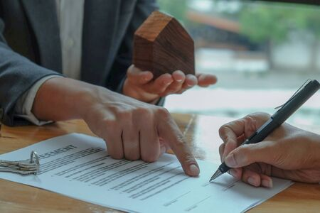 Businessmen selling the house pointing at the signing of the sales contract in the office. Stock fotó