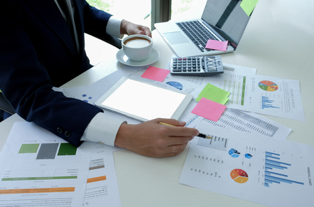 Businessman hand on coffee cup and uses a pen pointing at the graph on the desk in office. Stock fotó