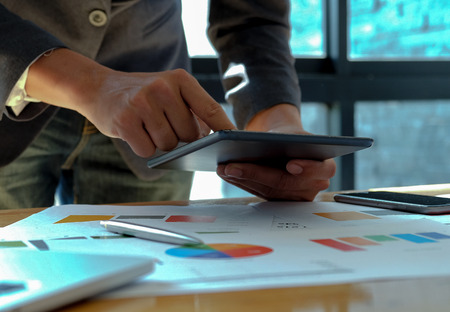 Hand businessman work on tablet in offices with graphs on the desk.