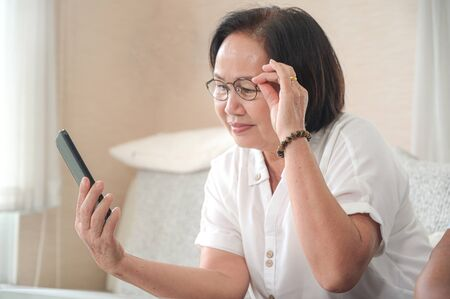Elderly asian woman sitting on sofa is calling a video call on smartphone. The other hand grabs the glasses.