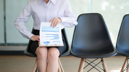 Girl sitting on chair preparing resume for job interview.