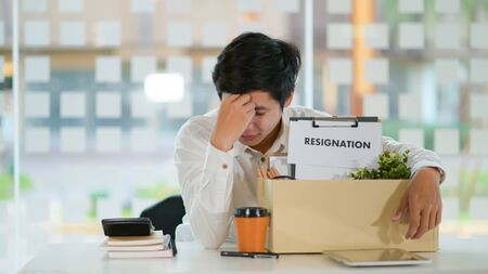 The concept of resignation, Male employee with a storage box for the equipment after resigning, He bowed face stressed.