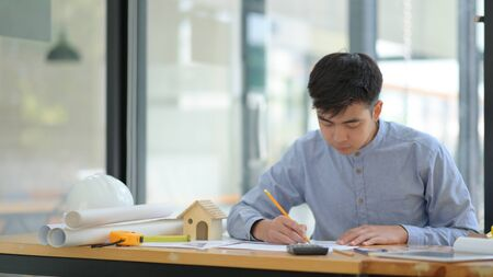 Engineering is checking floor plans in the office. He held a pencil in his hand and looked at the floor plan seriously. Foto de archivo