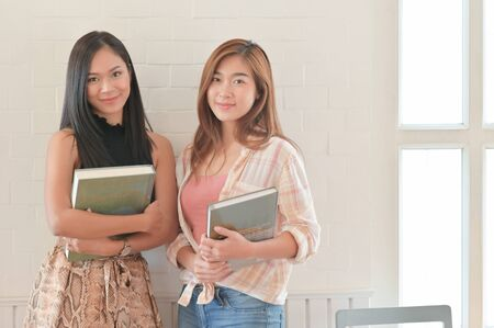 A portrait of a two Asian female students holding a book. They are preparing for university studies. 写真素材