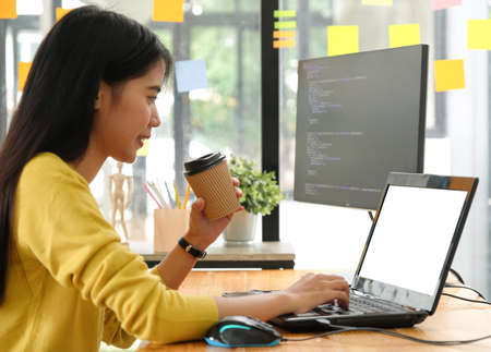 Young professional woman uses a laptop for work and online meetings, she works from home. Stock Photo