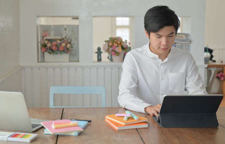 Male students are using laptop to study summer online at home,Work at home,Work from home.