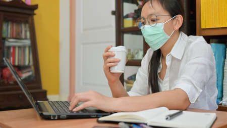 Cropped shot of  Asian woman is wearing a mask. She works at home to protect against Corona virus or Covid-19.