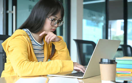 A female student with glasses is lacquer a lesson from her online study at home,Work at home,Work from home. Stock Photo