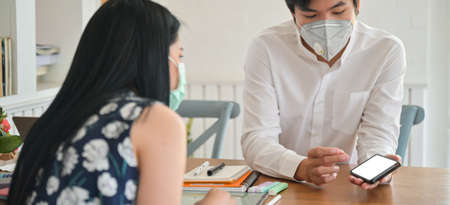 Male insurance agent wearing a mask is introducing a coronavirus health insurance package with a smartphone. Stock Photo