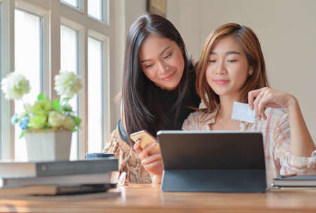 Two young female students with coffee are using a laptop to study online at home in the summer semester,Work at home,Work from home.