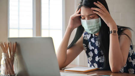 Girl wearing a mask and touching her head She works at home to protect against the Covid-19 virus.