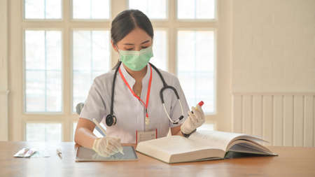 Nurses wear gloves and mask use tablet to record blood test results for covid-19 virus infected people.