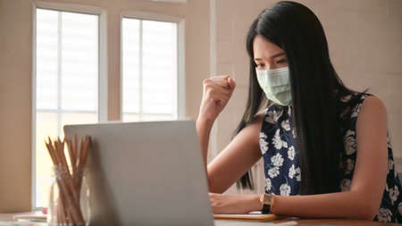 Girl wearing a mask with confident gestures.She works at home to protect against the Covid-19 virus. Stock Photo