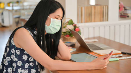Young woman uses a tissue to cover her mouth and sneeze in a cafe.She is at risk of spreading the Covid-19 virus.