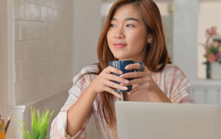 Teenage student smile and drink coffee while studying online from their home laptop.