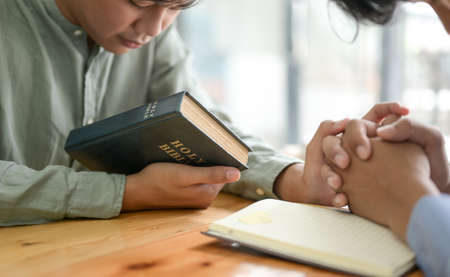 Close-up shot of The young man holding the bible and bowing to pray.