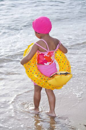 Little Girl with yellow lifebuoy on sand beach