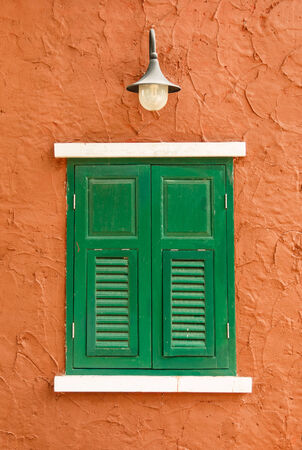Green window on orange wall background photo