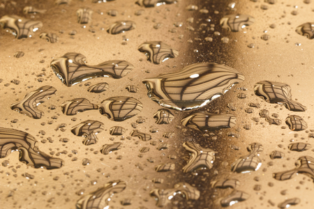 Pattern of water drops in a shiny metallic surface with table reflections photo