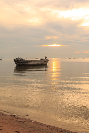 old boat in front of sunset background near beach photo