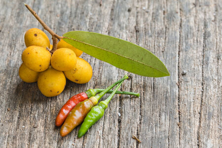 siamensis: Rauwenhoffia siamensis Scheff fruit  and chilis on wood Stock Photo