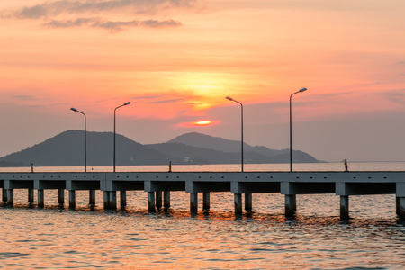 lamp post: Sunset behind Small port ship and lamp post Stock Photo