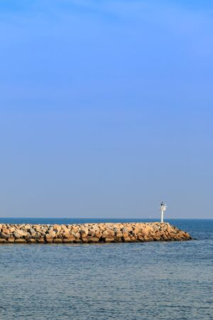 jitter: breakwater in the sea with  beacon light on it