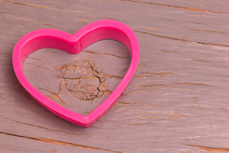 plastic heart: Pink plastic heart on a wooden floor