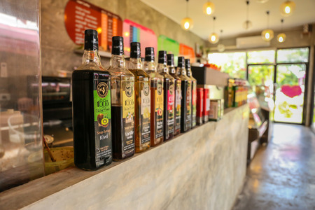 lined up: SATTAHIP, THAILAND – JUNE 5, 2015: Fruit syrup bottles lined up on a coffee shop shelf  in Coffee Beach Cafe, Thailand on 5 June 2015