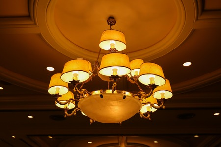pomp: Yellow lamps with brass structure on ceiling in ballroom